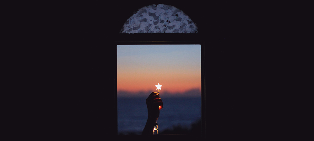 A Hand Holding a star in the middle of the window as Dawn comes up