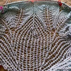 A shawl in progress. Lace netting toped with leaves in a blue-grey linen yarn.